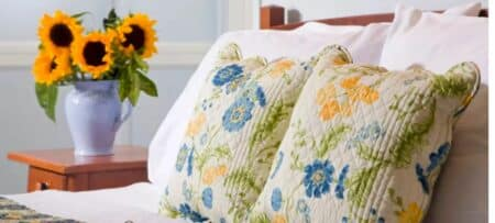 Guest bed with yellow and blue floral bedding, plump pillows and fresh sunflowers