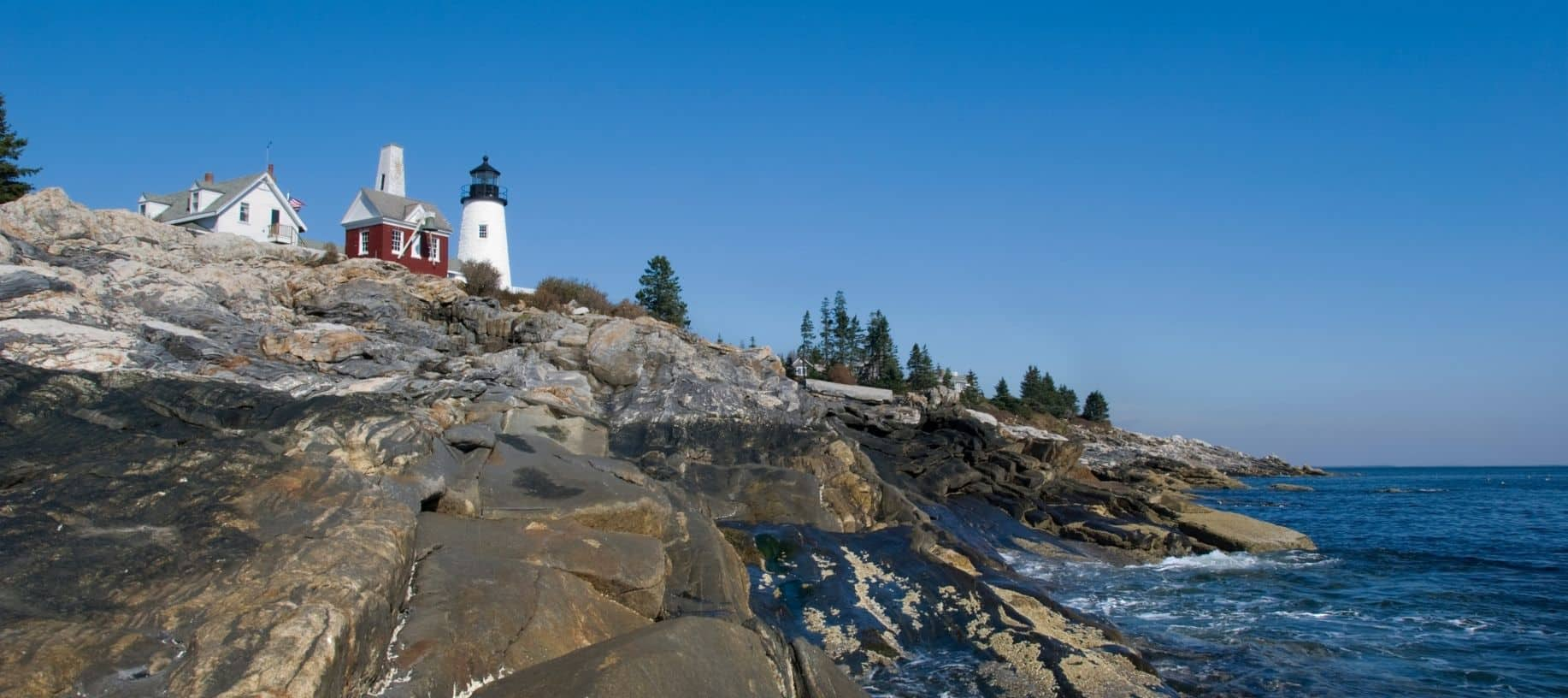 View of Pemaquid Point in Maine, a lighthouse on rocky mountain amidst blue skies
