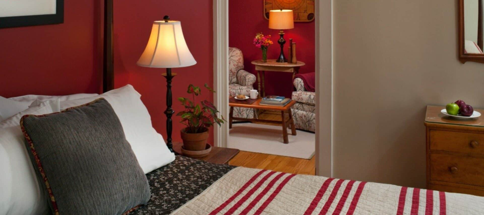 guest room with burgandy walls and striped comfortor