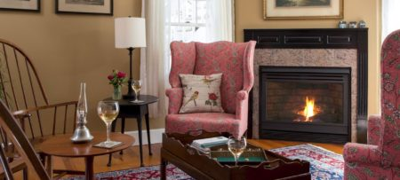 Sitting room area with rose wingback chairs and a fireplace.