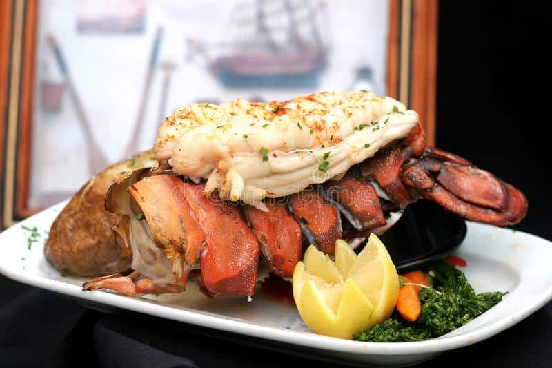 boiled lobster tail with baked potato and lemon on a white platter