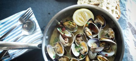 Frying pan full of fresh clams with fresh lemon juice and baked bread
