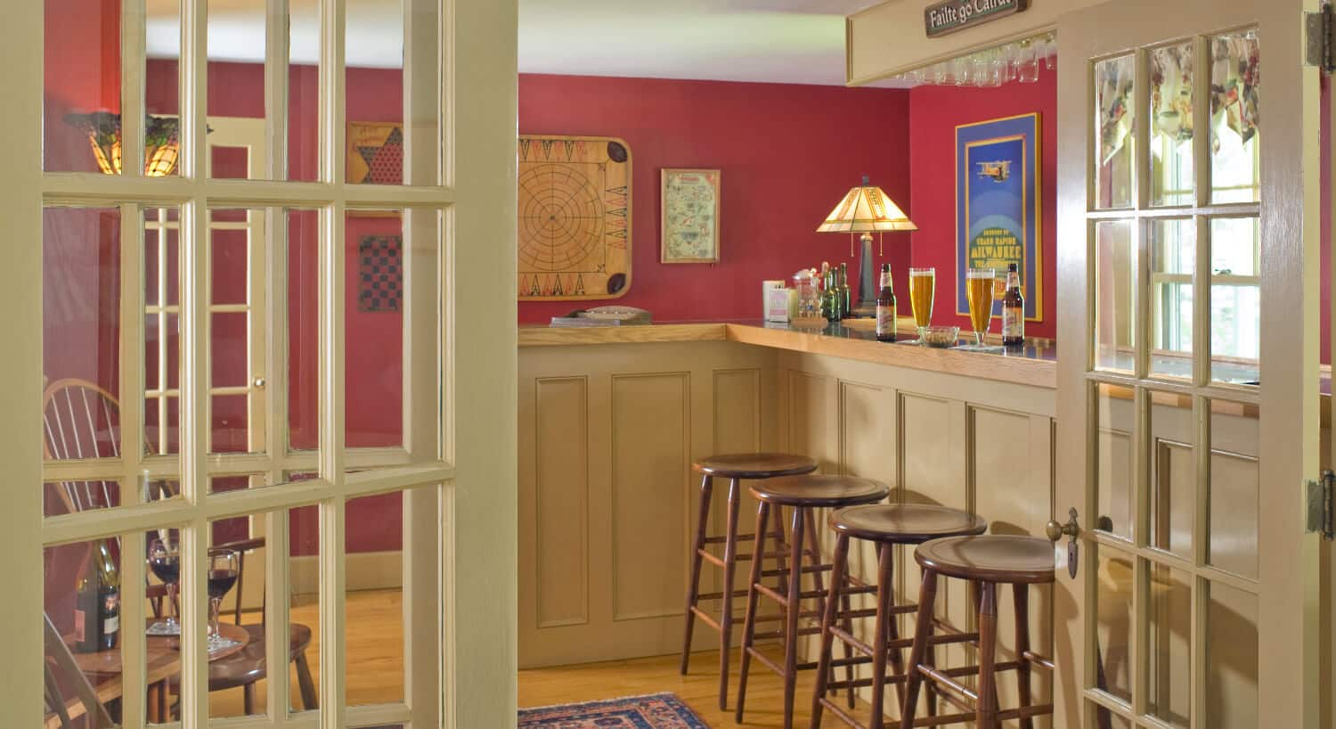 Tall bar with four stools in a room with red walls.