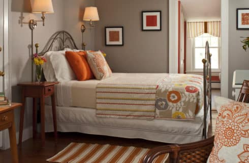 Clean and fresh bedroom decorated in grey and orange with a large brass bed and comfortable seating.