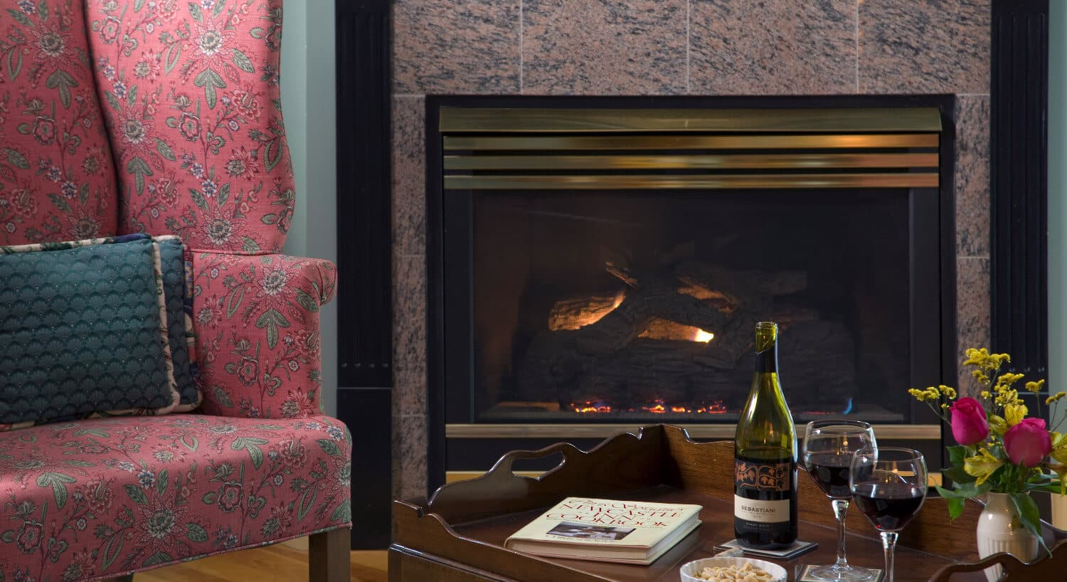 Wingback chairs sits next to a large fireplace fronted by a table with snacks and a bottle of wine.