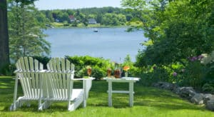 Two white adirondack chairs next to a small table on the grass overlooking the water.