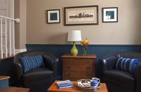 Two leather club chairs make up a seating area with a cherry dresser and coffee table.
