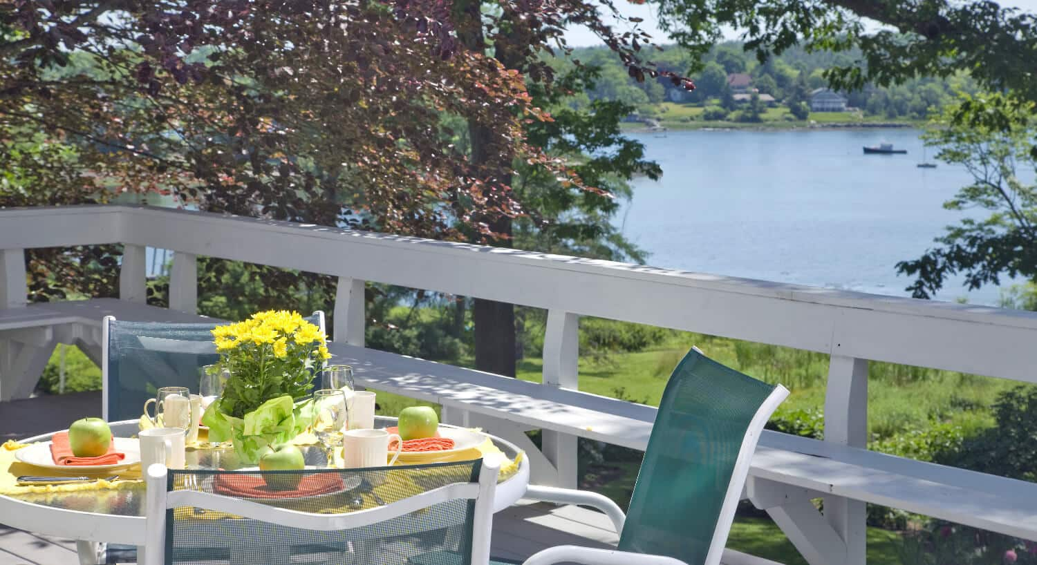 Small table and chairs on a deck set for breakfast.
