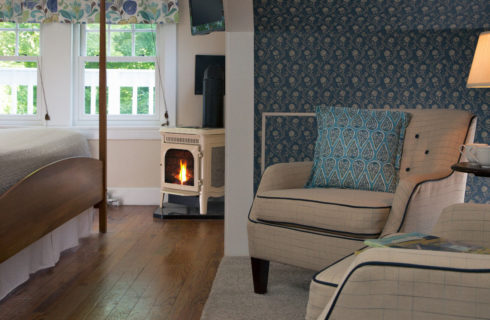 Bedroom with blue wallpaper, comfortable armchairs and a small gas stove.