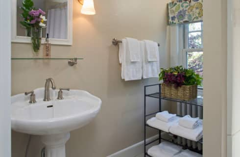 Bathroomw ith a white pedestal sink and mirror and a cart holding a plant and extra towels.