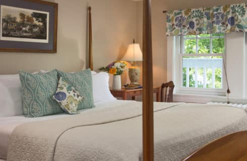 Large four-post bed made up in cream with decorative pillows next to a table and desk beside a large window.