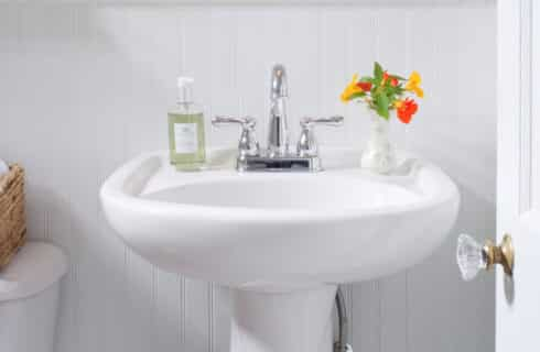 White pedestal sink with yellow and orange flowers in a vase and bottle of hand-soap.