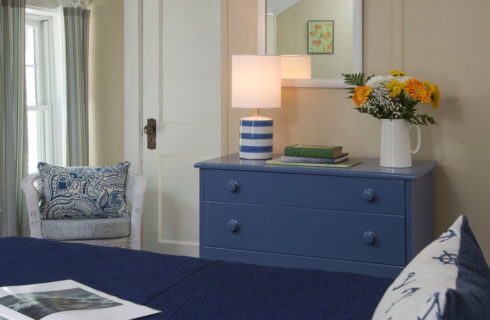 Cozy warm bedroom with a white iron bed made up in navy blue with a blur dresser and white wicker chair.