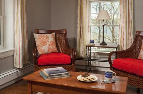 Wooden armchairs with red cushions forma seatign area with a wooden side table and coffee table.