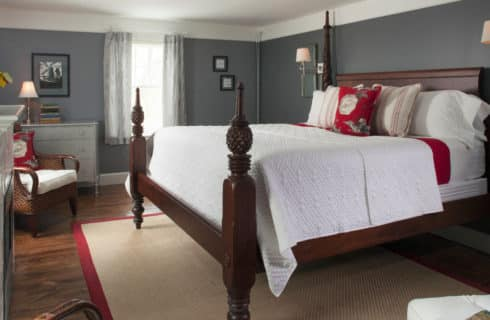 Large four-post bed made up in white in a room with grey walls and white crown molding.