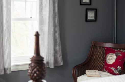 Detail of pineapple bed post next to a large window and wicker chair in the corner of the room.