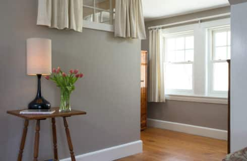 Detail of a table with a lamo in the bedroom painted grey with wood floors.