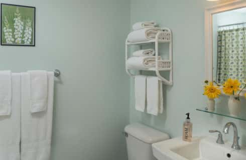 Bathroom with pale green walls, a pedestal sink, stool and towel racks.
