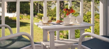 Deck with white rails holds a small white wooden table and chairs set with coffee cups and flowers.