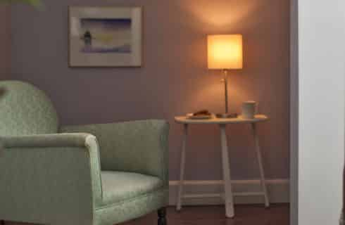 Pale green armchair in a lavender room with a small white side-table.