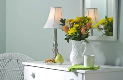 White dersser topped with a lamp and white pitcher filled with orange and yellow flowers.