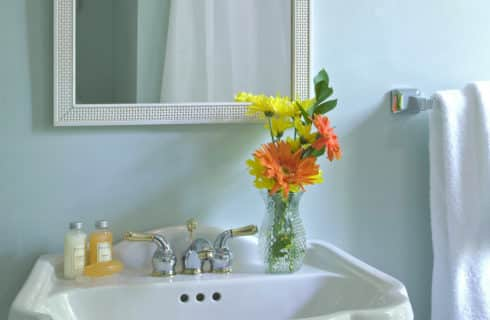 White pedestal sink with yellow and orange flowers in a vase topped with a white-framed mirror.