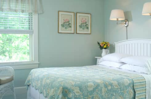 Bright and airy bedroom with pale aqua walls and bedding on the queen-sized bed.