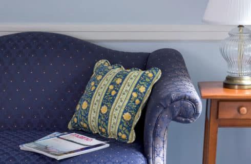 Blue coouch with decorative pillows next to a side table with a lamp.