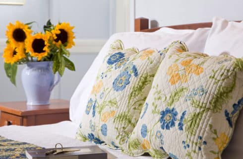 Bed with blue yellow and white shams alongside a bedside table with a vase full of sunflowers.