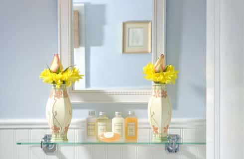 Glass shelf in bathroomw ith elegant vases full o fyellow flowers and a white-framed mirror.