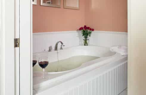 Deep soaking tub in white in a bathroom with peach walls