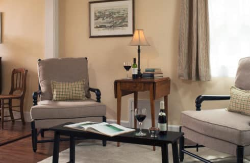 Two beige armchairs are joined by an end table with a lamp and a coffee table in a relaxing sitting area.