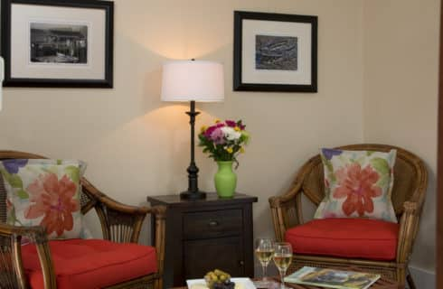 Wicker chairs with red cushions form a seating area with a small table n the corner of a bedroom.
