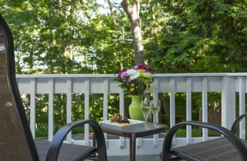 Small table and chairs on a deck with a white railing.