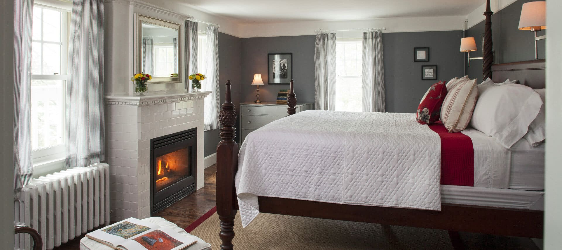 Large four-post bed made up in white in a room with grey walls and white crown molding and a white fireplace..
