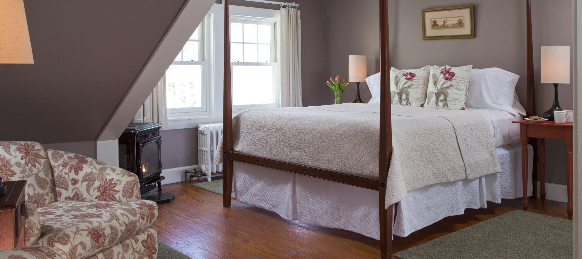 Gracious room painted in grey holds a large four-post bed with white bedding, and a small seating area under a pitched roof.