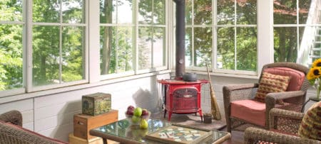 Sunny room with many windows holds cchairs, a table and a red wood stove.