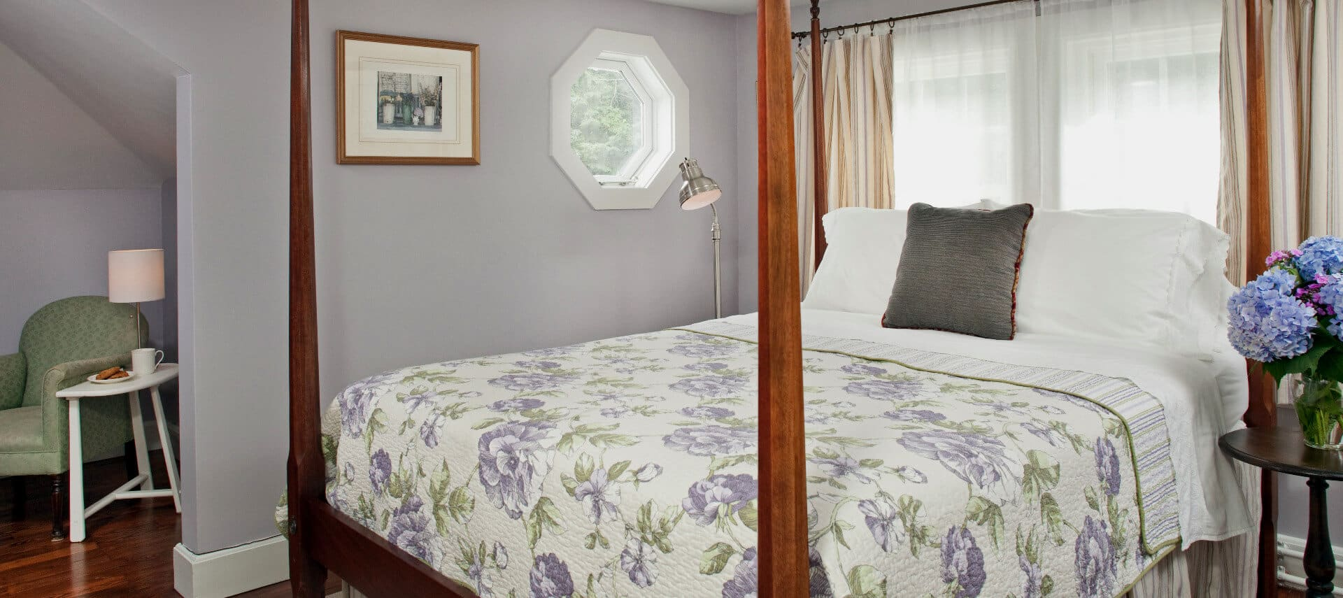 Bedroom painted in pale lavender with a cherry four-post bed made up in a lavender patterned cover.