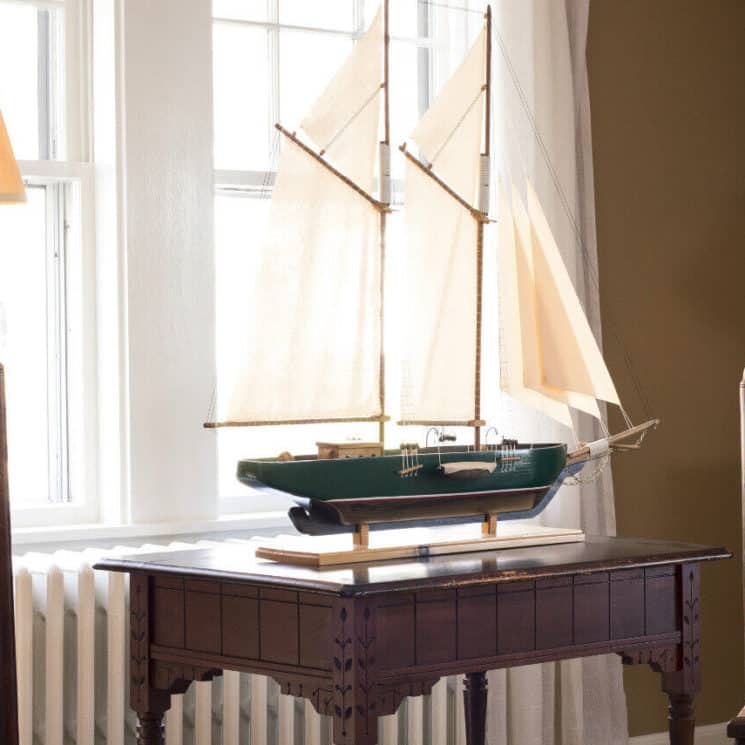 Sitting area in parlor with two wooden chairs an a model ship on a small table.