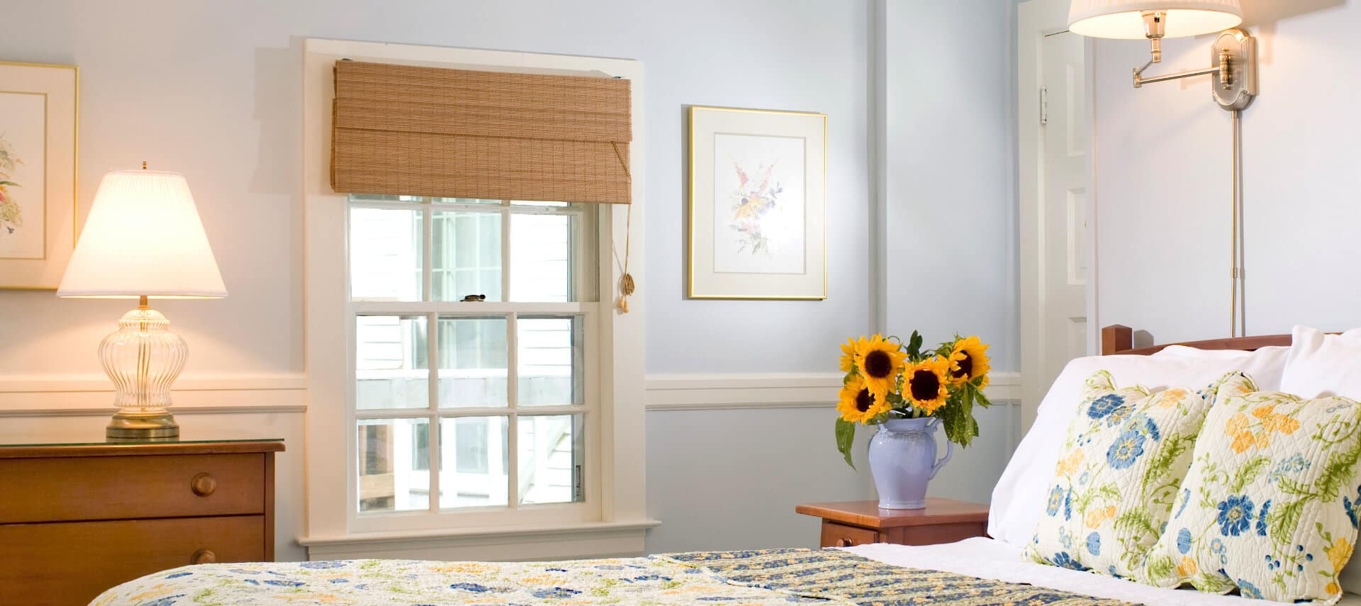 Bright cheerful bedroom with wooden bed made up in white yellow and blue quilt and shams with a large window and wooden dresser.