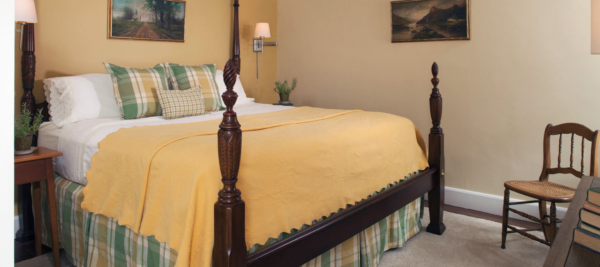 Large four-post wooden bed made up in clean linens in a roomw ith pale painted walls.