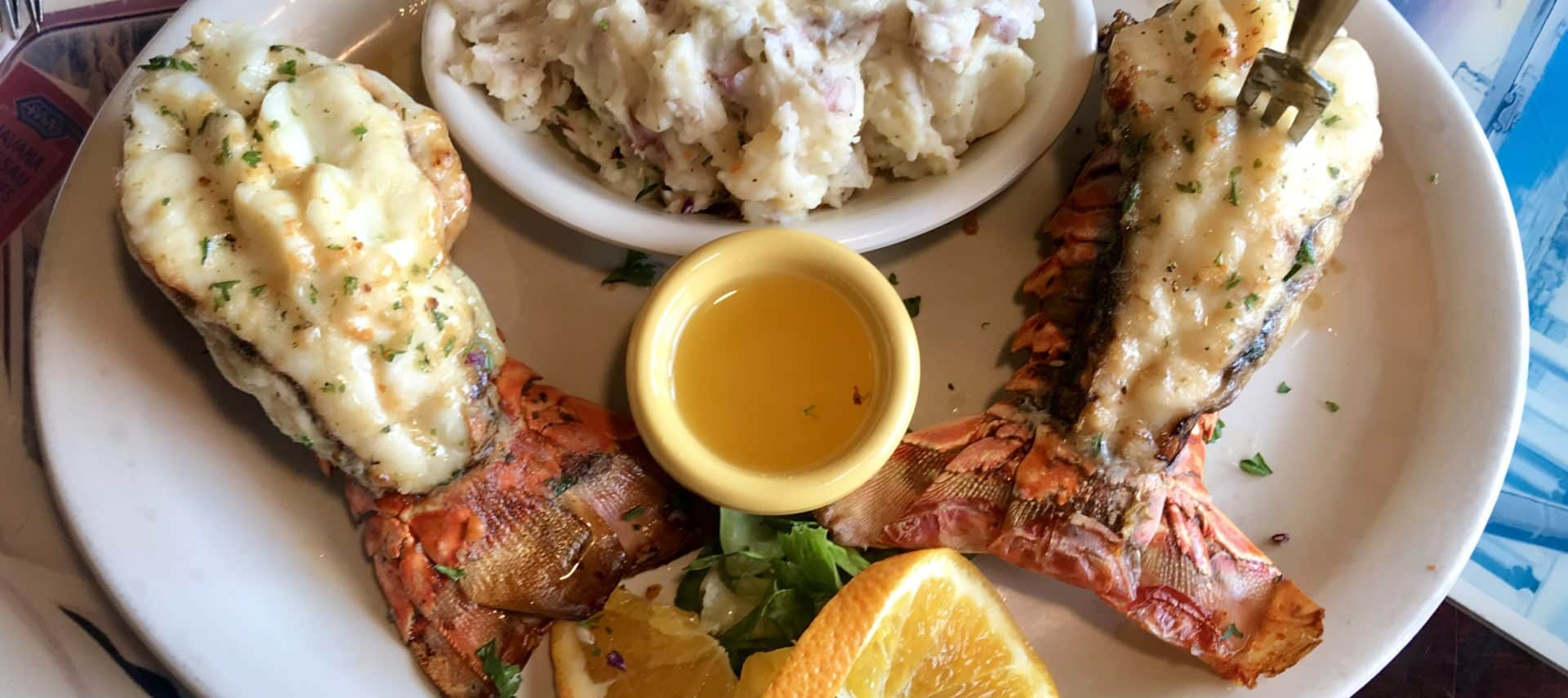 white plate topped with fresh cooked lobster, mashed potatoes, and dipping sauce