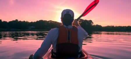 Man rowing a kayak in the early morning with a pink dawn sky