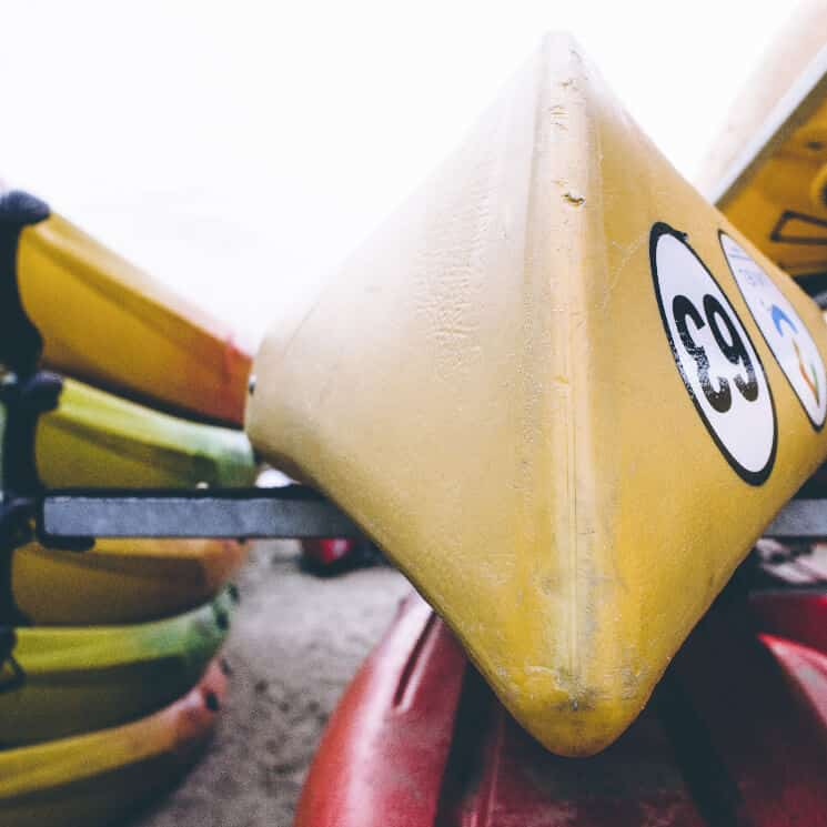 Red and yellow kayaks on a rack on the beach.