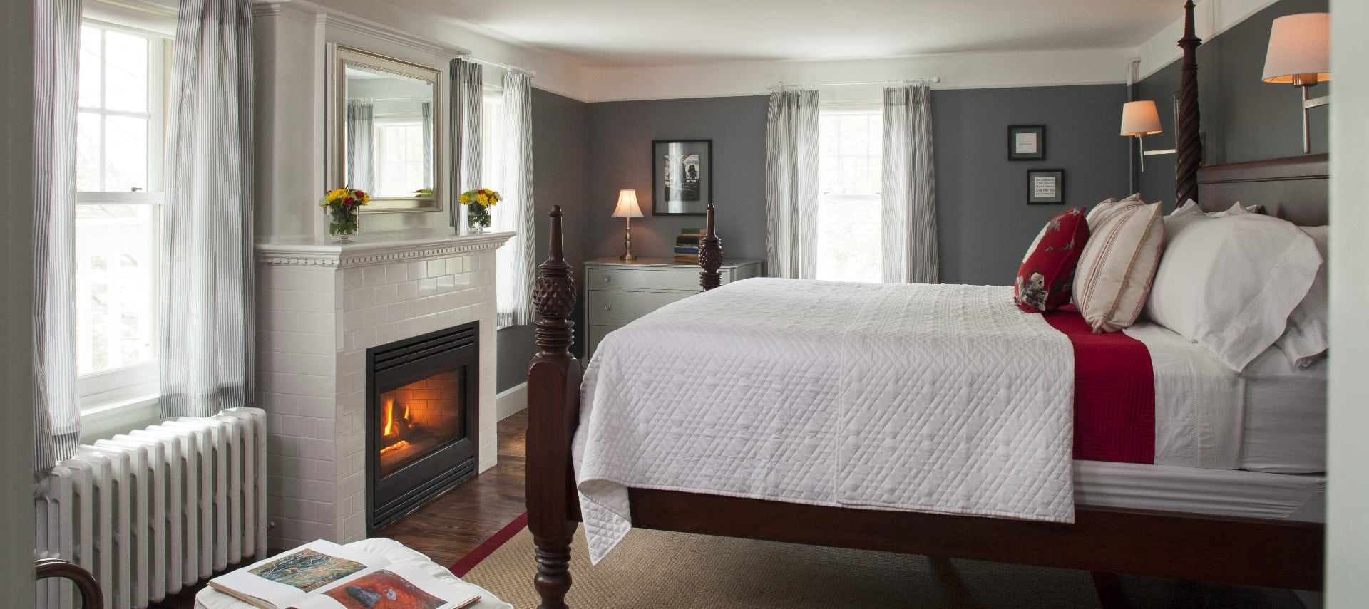 Large room with a fireplace and a wooden four-post bed made up in white