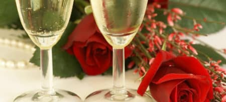 Champagne glasses filled with bubbly next to red roses on a white background.