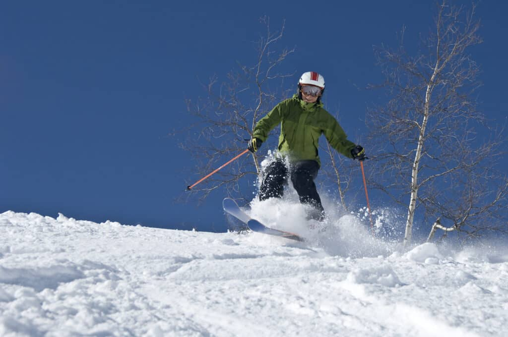 person in green parka skiing down a mountain against a blue sky